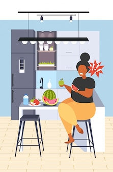 Donna obesa grassa che mangia anguria e mela dieta fresca della frutta ragazza afroamericana nutrizione sana perdita di peso concetto moderno cucina interno verticale integrale