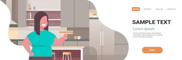 Donna paninoteca della holding della donna che mangia l'interno moderno della cucina di concetto non sano di stile di vita degli alimenti a rapida preparazione