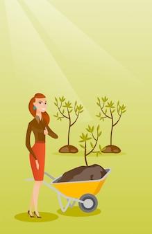 Donna spingendo la carriola con la pianta.