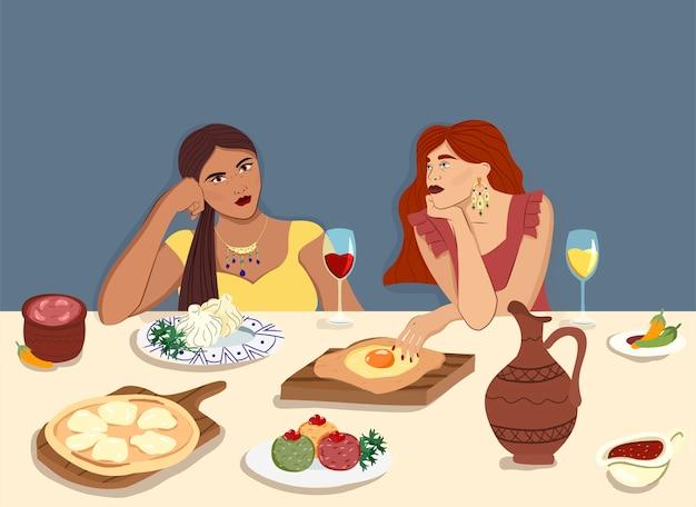 Donne a tavola che mangiano cibo tradizionale georgiano: khachapuri, khinkali e bevono vino rosso e bianco. concetto per ristoranti e turismo di cucina tradizionale georgiana.