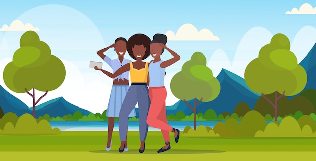 Donne che prendono la foto del selfie sui caratteri femminili della macchina fotografica dello smartphone che stanno insieme le ragazze all'aperto che posano sopra l'orizzontale integrale del fondo delle montagne del paesaggio della natura