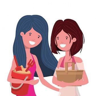Donne con costume da bagno e secchio di sabbia