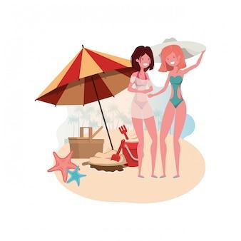 Donne con costume da bagno sulla spiaggia e ombrellone