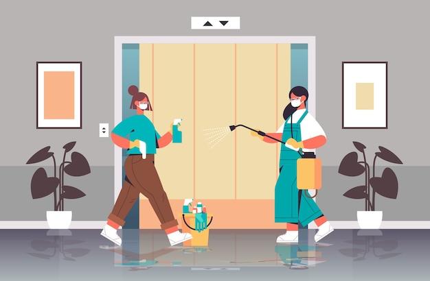 Donne delle pulizie in maschere che disinfettano le cellule di coronavirus in ascensore per prevenire la pandemia covid-19 servizio di pulizia disinfezione controllo dell'epidemia