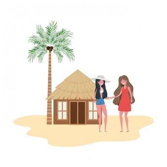 Donne in piedi in spiaggia con casa sulla spiaggia