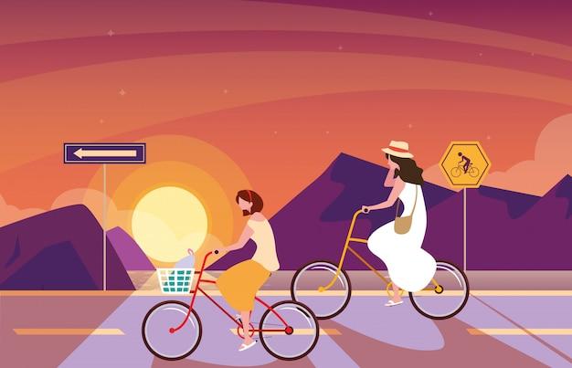 Donne in sella a bici nel paesaggio di alba con segnaletica per ciclista