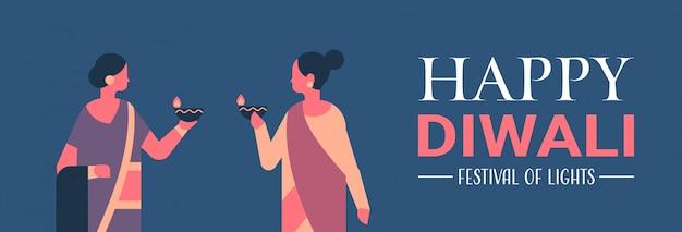 Donne indiane felici di diwali che tengono l'insegna di celebrazione della candela della lampada a olio