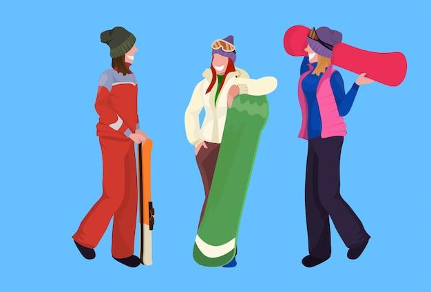 Donne sciatori snowboarder che tengono insieme dell'attrezzatura