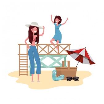 Donne sulla spiaggia con cestino da picnic