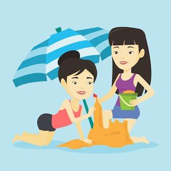 Due amici che costruiscono castello di sabbia sulla spiaggia.
