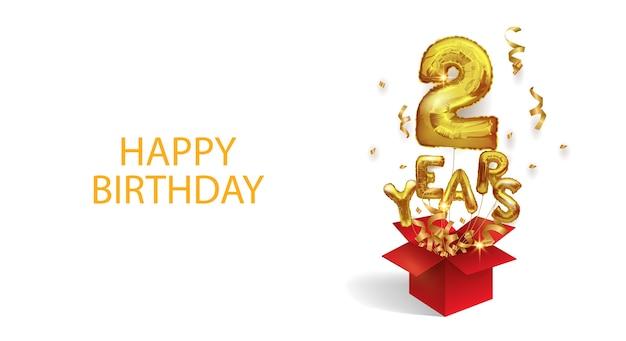 Due anni dalla nascita. numero 2 un palloncino di foil volante vola fuori da una scatola di coriandoli. festa di compleanno.