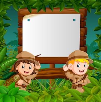 Due bambini su un'avventura nella giungla con sfondo di legno bianco