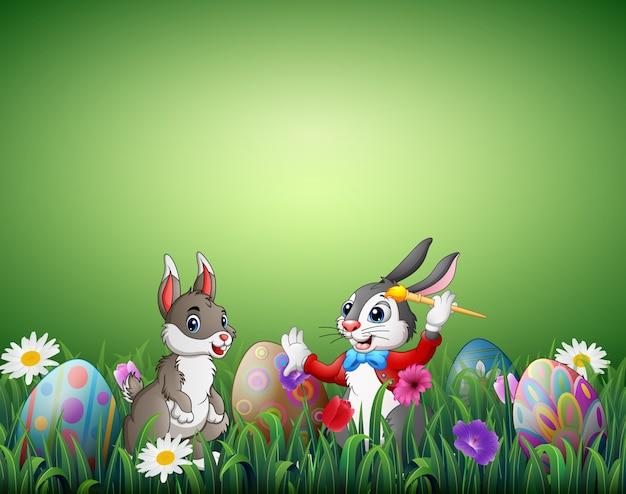 Due coniglietti pasquali con le uova di pasqua in un campo