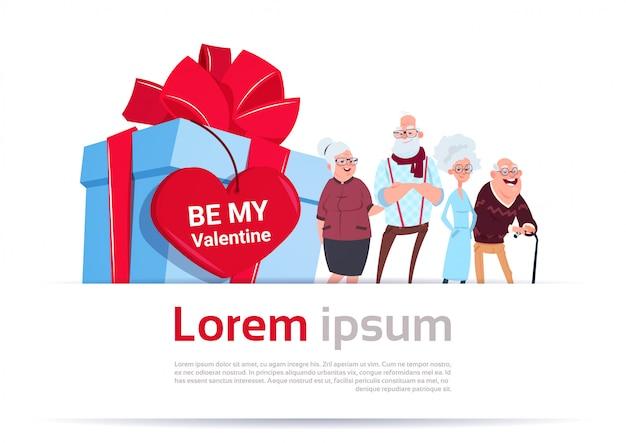Due coppie senior sopra il contenitore di regalo con l'etichetta di forma del cuore insegna felice del modello di concetto di giorno di biglietti di s. valentino