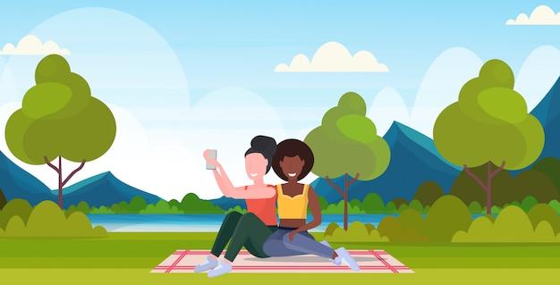 Due donne che prendono la foto del selfie sui caratteri femminili della corsa della miscela della macchina fotografica dello smartphone che si siedono all'aperto sull'erba che posa sopra l'illustrazione orizzontale integrale di vettore del fondo delle montagne del paesaggio della natura