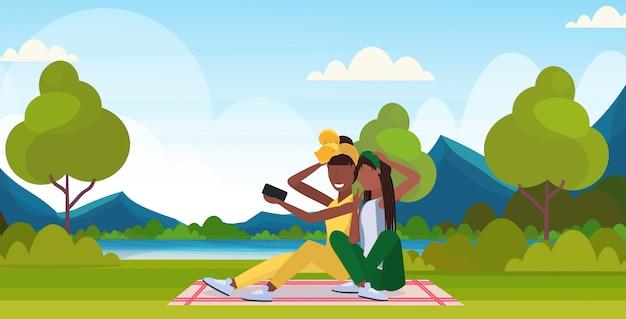 Due donne che prendono la foto del selfie sui caratteri femminili della macchina fotografica dello smartphone che si siedono all'aperto sull'erba che posa sopra l'orizzontale integrale del fondo delle montagne del paesaggio della natura