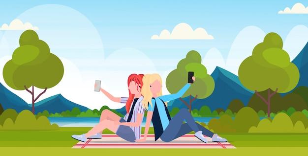 Due donne che prendono la foto del selfie sulla macchina fotografica dello smartphone i personaggi dei cartoni animati femminili che si siedono schiena contro schiena e che posano il fondo all'aperto del paesaggio della natura all'aperto