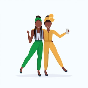 Due donne che prendono la foto del selfie sulla macchina fotografica dello smartphone personaggi dei cartoni animati femminili che stanno insieme posanti sul fondo bianco integrale