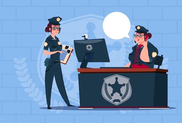 Due donne della polizia che lavorano alle guardie femminili uniformi d'uso del computer sul fondo dei mattoni blu