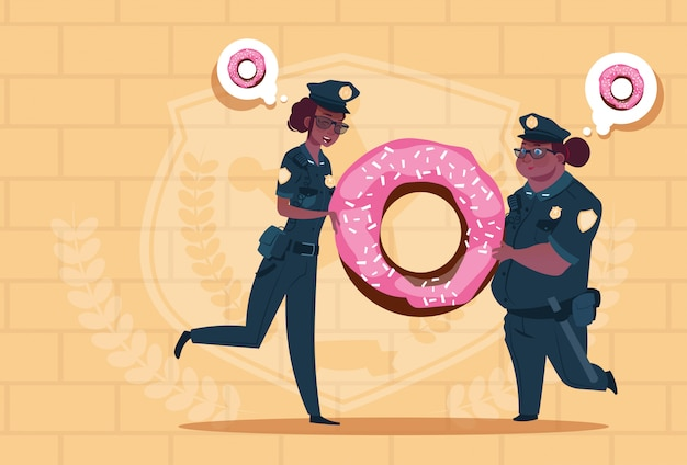 Due donne della polizia dell'afroamericano che tengono ciambella che indossa le guardie femminili uniformi sul fondo dei mattoni blu