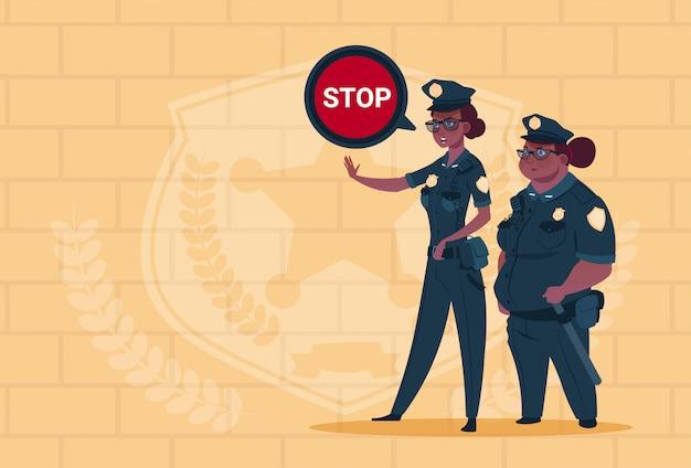 Due donne della polizia dell'afroamericano che tengono il fanale di arresto che indossa le guardie femminili uniformi sul fondo dei mattoni blu