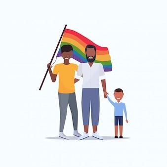Due giovani padri gay con figlio tenendo la bandiera arcobaleno gay stesso sesso coppia afro-americana con boy love parade lgbt orgoglio festival concept flat full length