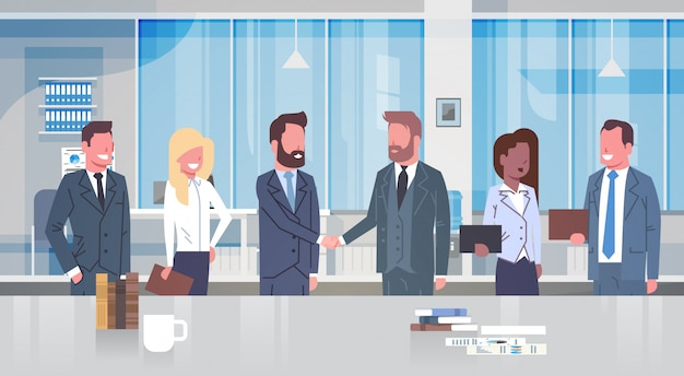 Due uomini d'affari che agitano le mani con gruppi di uomini d'affari in ufficio moderno partner mano scossa con