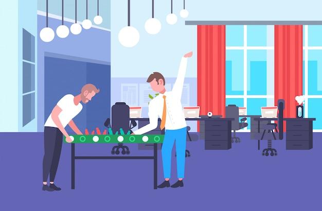 Due uomini d'affari colleghi che giocano a calcio balilla colleghi che si divertono insieme durante la pausa uomini d'affari relax ufficio centro di co-working interno orizzontale a figura intera