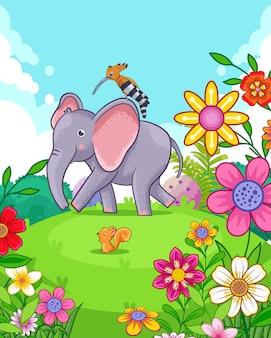 Elefante sveglio felice con i fiori che giocano nel giardino