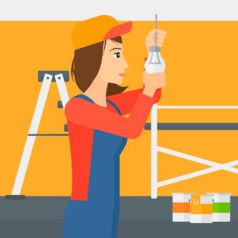 Elettricista torcendo la lampadina.