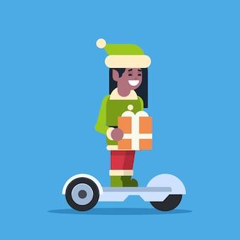 Elfo ragazza babbo natale aiutante giro scooter elettrico buon natale vacanza capodanno concetto piatta