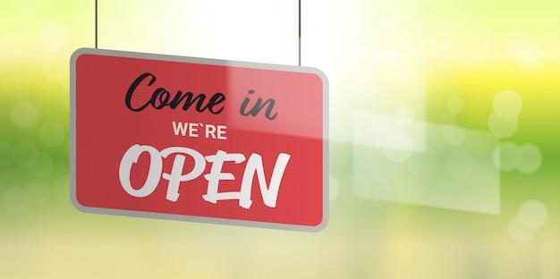 Entriamo, siamo un cartello pubblicitario aperto appeso sul vetro del negozio di vetrine apertura etichetta concetto con il testo