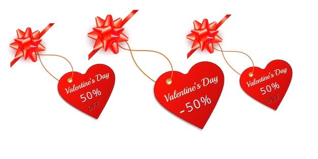 Etichetta rossa ed etichetta di vendita di san valentino nella forma di cuore con l'arco e il nastro del regalo isolati su bianco