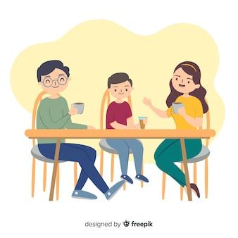 Famiglia disegnata a mano intorno al tavolo