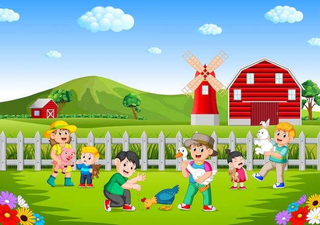 Famiglia e bambini che giocano in fattoria divertendosi