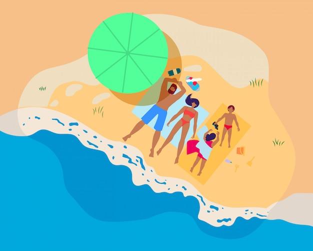 Famiglia felice che si distende sulla spiaggia alle vacanze estive