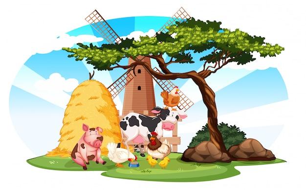 Fattoria di scena con animali da fattoria e mulino a vento in azienda