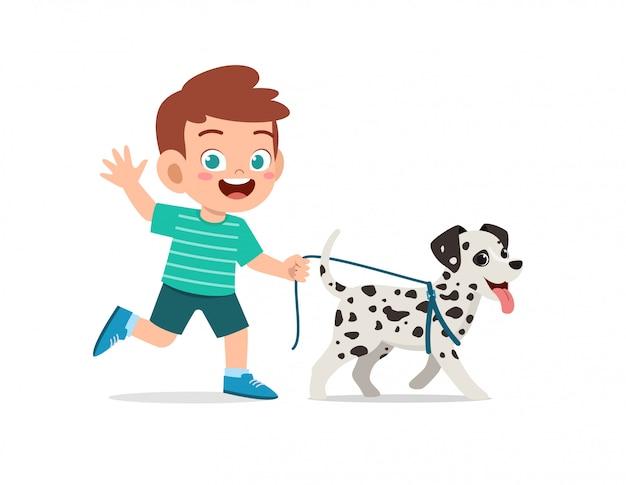 Felice carino ragazzino ragazzo ragazza gioca con il cane da compagnia