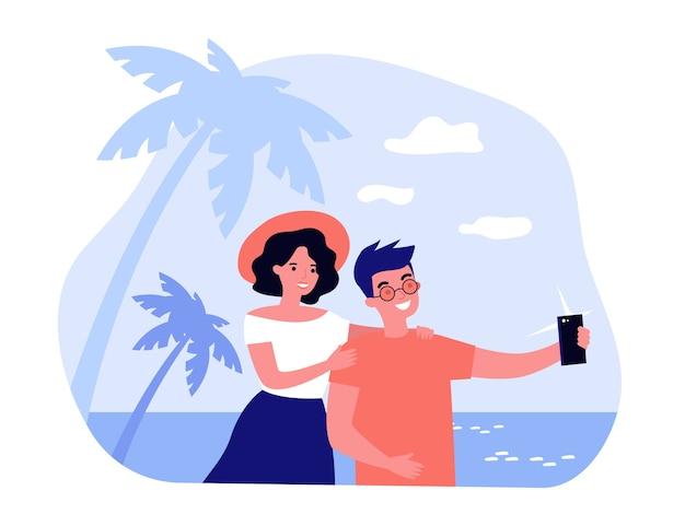 Felice coppia in viaggio prendendo selfie sul cellulare. turisti che camminano sulla spiaggia e si godono le vacanze estive. illustrazione per luna di miele, vacanze, concetti fotografici