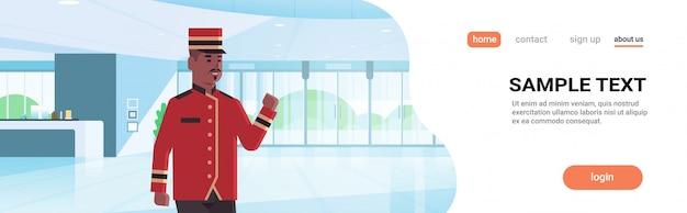 Felice fattorino lavoratore maschio in uniforme servizio alberghiero moderno reception area lobby interno personaggio dei cartoni animati afroamericano