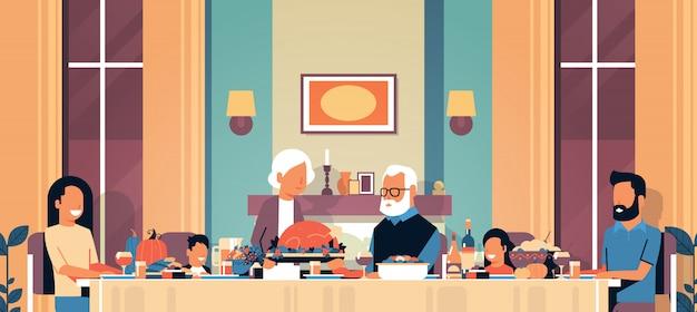 Felice giorno del ringraziamento tavolo di famiglia multi generazione seduto per celebrare il giorno del ringraziamento
