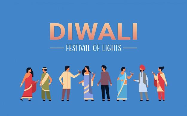 Felice gruppo di persone indiane diwali indossando abiti tradizionali nazionali tenendo banner olio