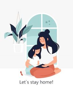 Felice madre bruna con una figlia che legge un libro a casa vicino alla finestra e il testo restiamo a casa!