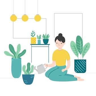 Femmina che innaffia le sue piante domestiche