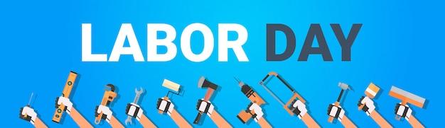 Festa del lavoro con le mani che tengono gli strumenti differenti. 1 maggio banner orizzontale di vacanza