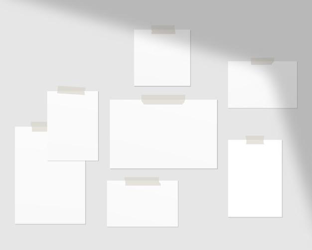 Fogli vuoti di carta bianca sul muro con ombra sovrapposta.