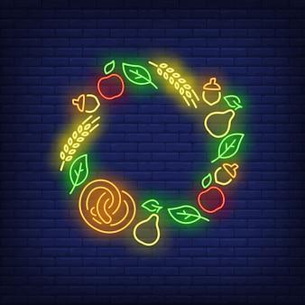 Foglie, mele, ghiande, pere, pretzel e orecchie incorniciano l'insegna al neon