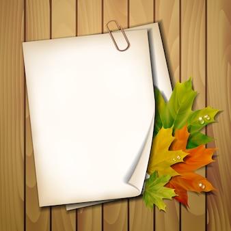 Foglio di carta con foglie di autunno su texture di sfondo in legno.