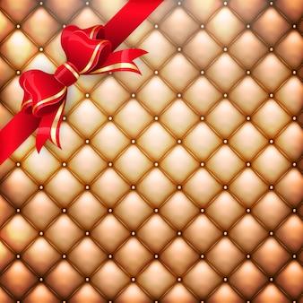 Fondo del modello di cuoio della tappezzeria realistico dorato con fiocco regalo rosso.