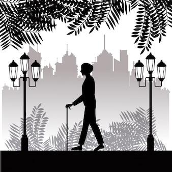Fondo della città del parco del bastone della passeggiata dell'uomo più anziano della siluetta